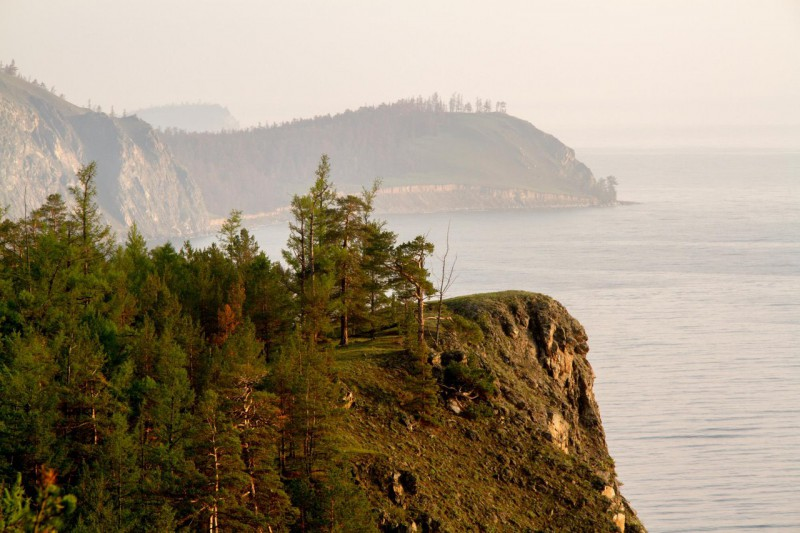 Байкал в дымке, из-за склона проглядывает остров Богучан. Автор: Александр Ермаков